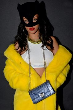 Rihanna teams black Batman mask with crop top vest and canary yellow coat for Jeremy Scott's Moschino party at PFW