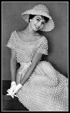 Sondra Peterson in charming white organdy embroidered in tiny florets, waist is tied in white satin, wide-brimmed hat of same material, by Christian Dior (Yves Saint Laurent), photo by Pottier, 1959