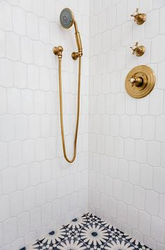 White tile shower with brass fixtures