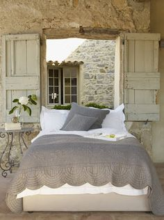 I love the romantic old world feeling that the stone and shutters give to this bedroom.