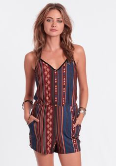 Silky smooth romper featuring a burgundy, green, blue and yellow geometric pattern with black piping. Finished with a strappy back design and hidden side pockets. Style with booties and an open f...