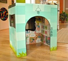 Make-Shift Playhouse tutorial - inside of box is decoupaged with book pages from childrens books & outside is decoupaged with painted paper - could use scrapbook paper, comic book pages, or just paint