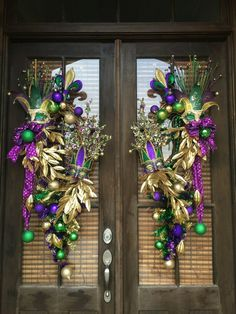 Custom Mardi Gras grapevine wreath with Mardi Gras mask, swags, gold bay leaves. Designed by Master Designer Nichole Lefebvre.