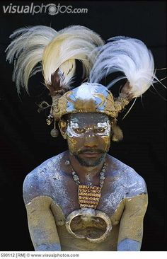 Aboriginal man wearing tribal headdress with feathers from King of Saxony Bird of Paradise (Pteridophora alberti) Papua New Guinea