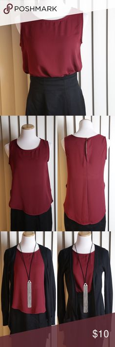 Beautiful burgundy tank Awesome staple for any wardrobe. Wear it with a blazer to work. Ditch the blazer and tie it up for a night out. Wear it with a comfy cardigan for a casual, effortless look, or just wear it solo as the cute tank that it is! Slightly longer, tunic length.   Fun fact: this exact tank was actually worn by a model for an international Moët champagne ad!  Wine, red, cardinal, maroon Tops Tank Tops