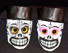2 papier mache skull masks with top hats