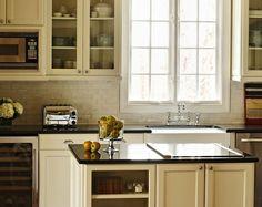 kitchens - ivory kitchen cabinets polished Absolute Black granite countertops farmhouse sink polished nickel bridge faucet glazed ivory subway tiles backsplash