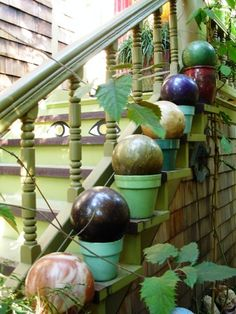 Bowling balls sitting on colored pots.  Very zen.