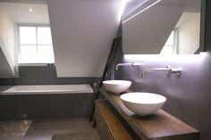 Moderne badkamer in Ulicoten met een massief eiken maatwerk badmeubel, boomstamblad, maatwerk spiegel met LED verlichting, bad, inloopdouche en betonciré op de wanden en vloer! #badkamerstudio #badkamerstudiobreda