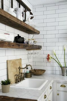 Subway tile kitchen. Check out these wide wood beams as shelving in a kitchen. It has a very organic feel to it.