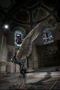 """Lit only by the stained glass windows of Westminster's Holy Church, Paul Fryer's """"Lucifer (Morningstar)"""", hangs, bound by power lines."""
