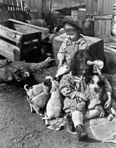 A couple of farm kids take care of the new puppies, one feeding while the other one snuggles, late 1900s or early 1910s. Photo: Underwood Archives, Getty Images / Archive Photos
