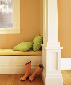 Orange Wellies, apple-green throw pillows, and spicy walls complete a cheerful seasonal color combo for an inviting nook. | @voiceofcolor Allspice PPG1207-6