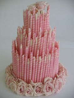 Chocolate wedding cake with pink & white candy striped cigars.