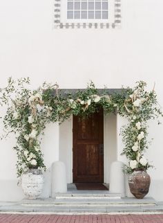 Two large planters with a climbing vine to frame the front doorstep or front window