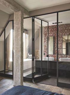 Jouant de transparence grâce à une verrière, la salle de bains aux murs de briques s'est dessiné un espace dans l'espace. Miroirs coupés sur place aux dimensions.