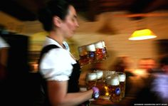 A waitress brings glasses of beer to the heads of the six Munich breweries as well as the owners of the Oktoberfest tents for the annual beer tasting prior to the 2014 Oktoberfest in the cellar of the Munich Beer and Oktoberfest Museum (Photo: Alexander Hassenstein/Getty Images)