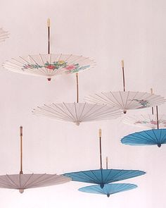 Inexpensive paper parasols can be hung from the ceiling for a stylish, exotic vibe. (marthastewartweddings.com)