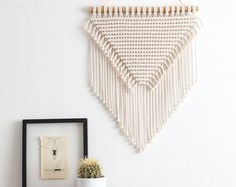This macrame wall hanging is hand-knotted using 100% cotton cord (braided, 5mm) in natural ecru with a bamboo supporting rod.  Approx Dimensions >  Width: 51cm / 20 inches Length: 99cm / 39 inches