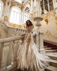 As far as we're concerned, this feathered Malyarova Olga #weddinggown and splendent surroundings are gilded perfection! | Photography By: Janna Kuzko | WedLuxe Magazine | #wedding #luxury #weddinginspiration #luxurywedding #bridal #fashion #weddingdress #gown