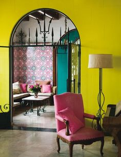 Stunning use of color in this gorgeous Spanish-inspired home with traditional wrought iron accents, a painted yellow tile wall, bright pink arm chair and patterned tile accent wall, and teal archway down the hall. Style At Home, Deco Cool, Living Spaces, Living Room, Interior Exterior, Interior Livingroom, Interiores Design, Home Fashion, Home Decor Inspiration
