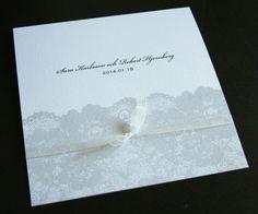 Ett inbjudningskort tryckt spets på pärlemopapper. Vitt organzaband.  Wedding invitation - lace