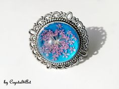 """The adjustable ring """"Flower in the spring sky"""" is made with naturally dried flower, immortalized in glass cabochon. See more of my creations on Adjustable Ring, Dried Flowers, Jewerly, Enamel, Sky, Turquoise, Spring, Metal, Glass"""