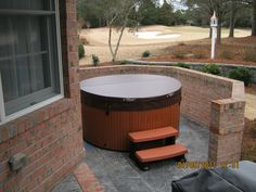Round Hot Spot Hot Tub Installation. This Hot Spring Grandee is tucked into a beautiful pergola and stone patio. Hot Tub Installation Ideas from Atlantic Spas and Billiards!