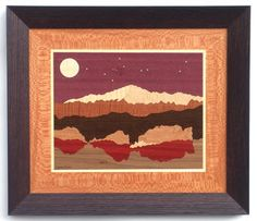 """Pikes Peak above Garden of the God's rock formation wood inlay/marquetry. Named for explorer Zebulon Pike, this majestic mountain graces the Colorado Springs skyline. The woods used in this scene are: Purpleheart, Brass, Sycamore, Sycamore, Curly Maple, Makore, Wenge, Cherry, Bloodwood, Figured Walnut. Stars are brass. Size: 18"""" x 21"""". Available in other sizes, borders and frames - see website."""