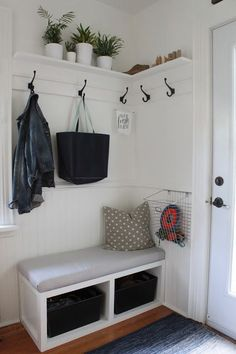 Small bench, hooks on wall with small shelf. Even like the wire basket. Throw gloves and hats in there?