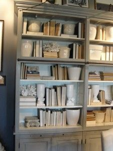 one of my favorite articles on styling bookcases.  She includes a wonderful tip… grouping paperbacks and small books in baskets and flipping them so that the pages face out.  I love it because it creates texture and art on a shelf, but it's still easy to pull the basket off the shelf and find what you're looking for!