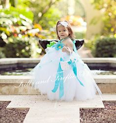 This adorable elegant tutu dress features soft white tulle covered in aqua criss cross. Three aqua flowers complement this tutu and an aqua satin ribbon is tied around the neck in a ribbon bow by Frills and Fireflies