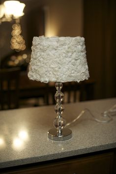 DIY rosette lampshade.   Find the rosettes in the ribbon section of JoAnns (other colors, too)... sold by the yard just like ribbon. Wrap it in rows up the lamp shade (cutting it at the seam of the lamp shade each time and starting a new row) and secure with hot glue.