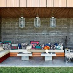 At her Hamptons home, interior designer Muriel Brandolini fashioned a colorful sitting area using a long custom-made teak sofa topped with vibrant accent pillows.
