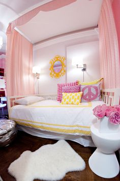 For Kate:  girl's rooms - pink drapes diy canopy white West Elm overlapping squares daybed ikea sheepskin pelt white modern hourglass stool accent table white bedding yellow frame hot pink yellow pillows silver Moroccan pouf polished nickel wall sconces Ikea Rens