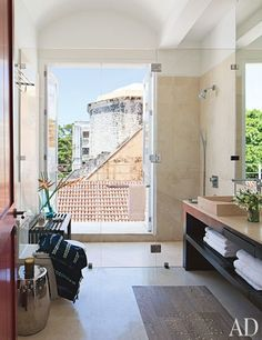 The light-filled master bathroom boasts a shower with a view of Cartagena's terra-cotta-tile rooftops | archdigest.com
