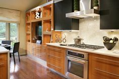 Perfect balance of black and maple with the high gloss backsplash and stainless appliances. The cooking space flows seamlessly with the rest of the house.