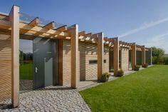 Dřevo vystupuje z domu v podobě sloupů na patkách, které oživují poklidnou dřevěnou fasádu.