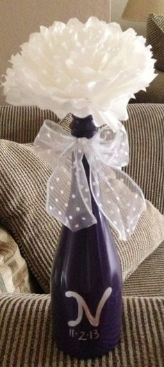 Spray painted wine bottles as center pieces with coffee filter flower for wine themed bridal shower.