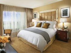 stilvolles Schlafzimmer in Gold mit gepolstertem Kopfteil am Bett