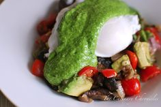 breakfast poached eggs over sauteed mushrooms, tomatoes, onions and garlic, topped with arugula pesto