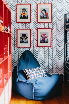 A denim beanbag chair and tiny heroes art pop against boldly patterned wallpaper in this shared boys' bedroom on HGTV.com.