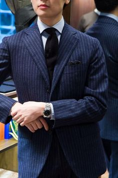 Navy pin-stripe suit with 3-roll-2 jacket, light blue shirt, black knit tie, and patterned PS. Navy all day, every day.