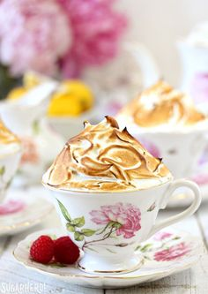 Lemon Meringue Teacup Cakes -lemon cupcakes baked right in teacups! Filled with raspberry jam and lemon curd, and topped with a big pile of toasted meringue. | From SugarHero.com