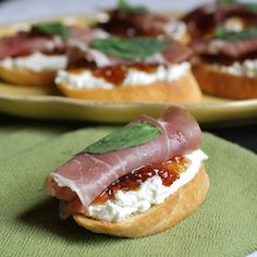 Crostini with goat cheese, fig jam, prosciutto, basil.