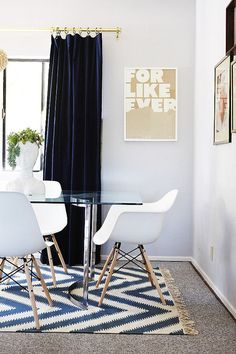 Glass dining table with white Eames chairs and chevron rug