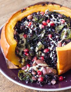 This stuffed squash is perfect for a vegan Halloween meal! It's one of the most warming, vibrant dinners for these darker, colder evenings too. The squash are stuffed with a mix of black rice, artichokes, cannellini beans, kale, almonds, lemon, garlic and thyme, and then topped with pomegranates and a drizzle of tahini to create something delicious!