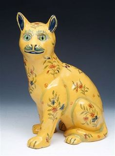 "A GALLE STYLE CAT, seated, on a yellow ground, applied glass eyes, and decorated with sprays of flowers, 12"" high"