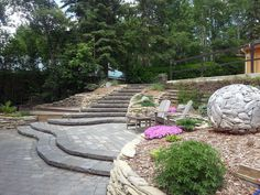 Stone steps and rock walls lead you down into the yard and patio.  A outdoor sculpture adds and interesting focal point to the yard.  Lakeside Cottages by Creative Landscape & Design