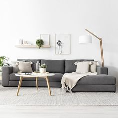 This simple grey couch in this very white space makes it super Scandinavian. I l